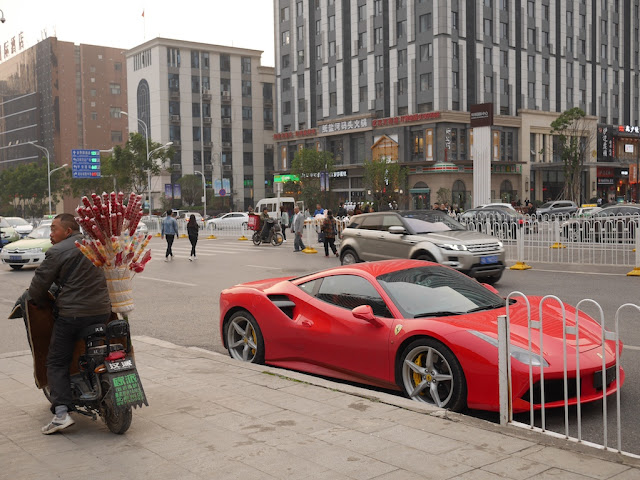 man on scooter selling candied fruit next to a red Ferrari