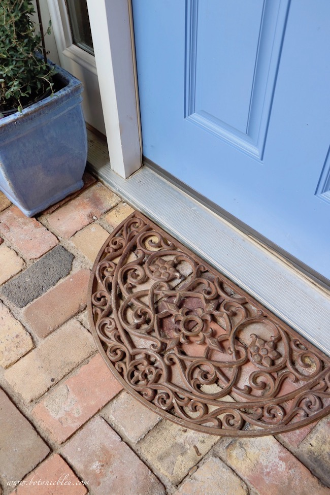 fall front porch decorating ideas with iron door mat on antique brick porch