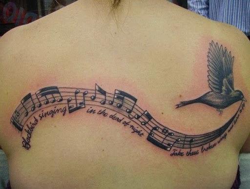 As Notas da música e Letras com um Pássaro está Voando Tatuagem Nas Costas