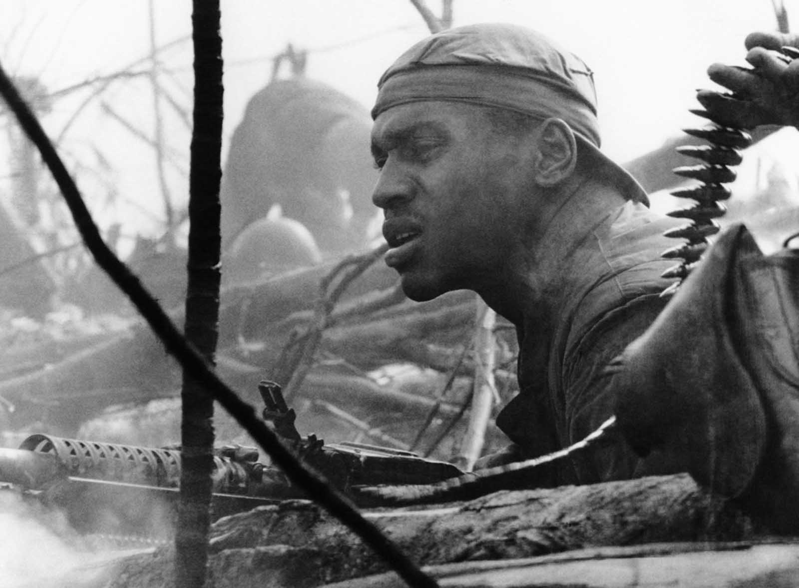 A grim-faced U.S. Marine fires his M60 machine gun, concealed behind logs and resting in a shallow hole, during the battle against North Vietnamese regulars for Hill 484, just south of the demilitarized zone, on October 10, 1966. After three weeks of bitter fighting, the 3rd battalion of the 4th Marines took the hill the week of October 2.