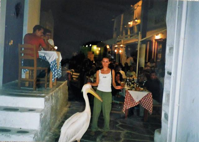 na greckiej ulicy przy tawrnie wypełnionej turystami kobieta pozuje do zdjęcia wraz z pelikanem