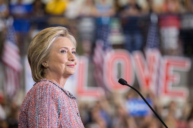 image of Hillary at a campaign event, standing on a stage smiling, while the crowd holds up large letters spelling LOVE in the background