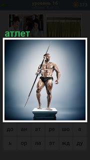 мужчина атлет с копьем стоит на постаменте с голым торсом