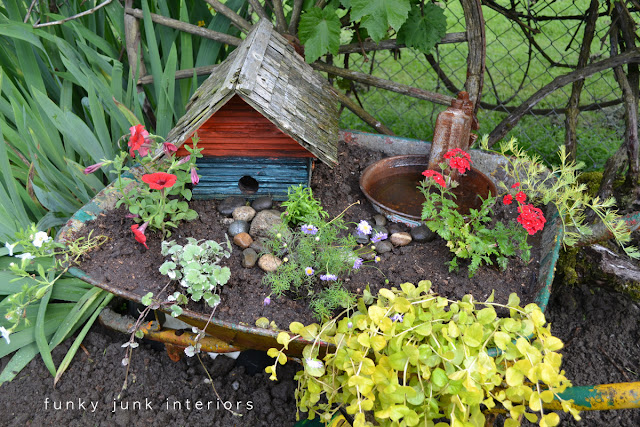 wheelbarrow flower bed with a birdhouse fairy garden