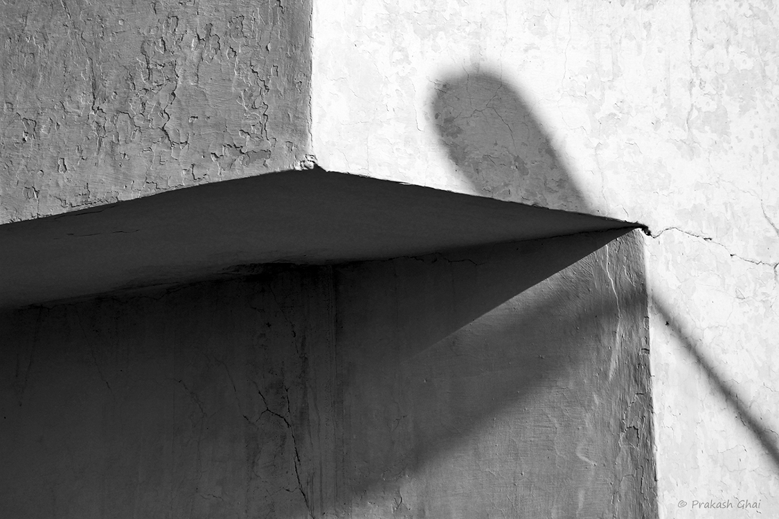 A black and white Minimalist Photo of a Street Lamp's shadow on the corner of a building.