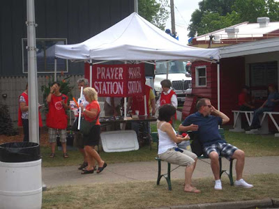 Large red banner with white letters reading Prayer Station, volunteers in red tshirts around it