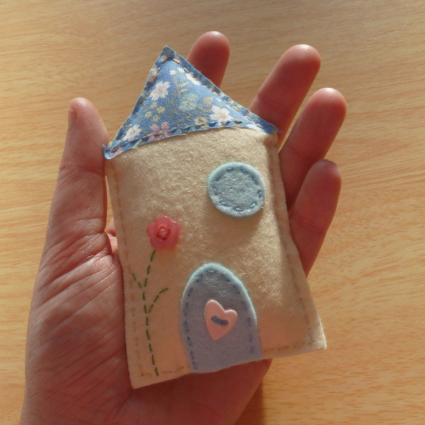 Miniature felt house hand sewn and held in hand learn how to make your own with this DIY craft tutorial by craftymarie