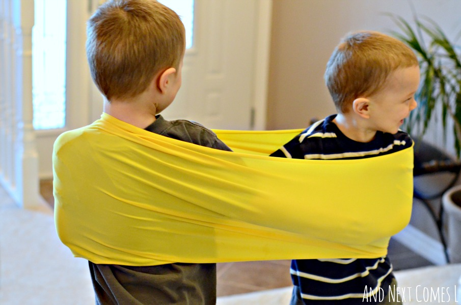 Using homemade stretchy resistance bands with more than one child to stimulate proprioceptive sensory input from And Next Comes L