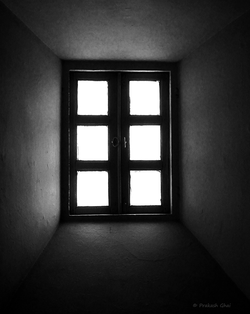 A Black and White Minimalist Photograph of a Window with 6 Panes illuminating Light.