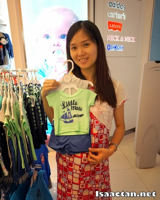 Janice happily holding onto one of the cuter boy clothes