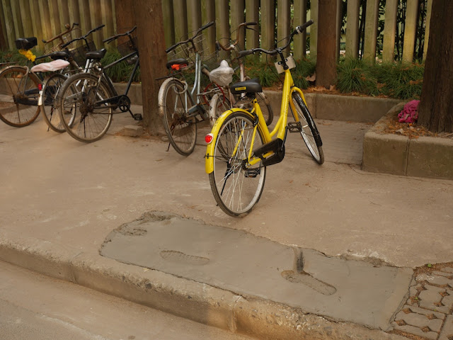 bike parked in a perfect location to guide people into walking on the wet concrete