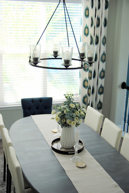 dining room, mix and match dining chairs, white decor, teal decor, aloof gray, curtain panels, drapes, curtains, faux floral, faux flowers, DIY, vintage rug, utah, table setting, tablescape, blue design, blue decor, teal, white, utah blogger, utah, blogger, chalk paint, painted dining table, painted furniture, how to hang curtains, how to style a dining room, best gray paint, favorite paint color, simple decorating, simple design, 8 chairs, 6 chairs, table that seats 8, captain chairs, dining room lighting, progress lighting, debut chandelier, six light chandelier, 6 light chandelier, black chandelier, exposed light bulbs, floating shelf, floating shelf dining room, minted art, water color art, water color painting, sunburst mirror, table runner, gray rug, safavieh rug, affordable design, design on a dime, laminate wood floors, flooring, cheap flooring, cheap hardwood, hardwood, laminate hardwood, wood stair treads, white risers, stairs, wood stairs, laminate stairs, colorful design, white dining chair, white chairs, modern design, traditional design, gray flooring, gray laminate, gray hardwood, gray stain, gallery wall