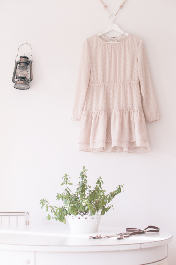 a bright white room with a dress and a storm lantern hanging