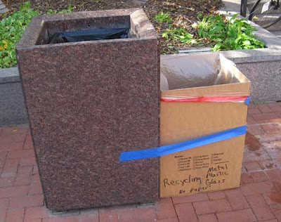 Stone trash container with cardboard box taped to it with blue tape, labeled Recycling