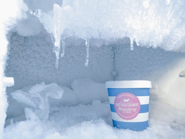 Open freezer compartment with tub of ice cream at the forefront