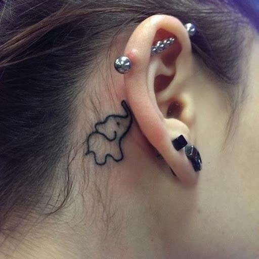 Um estilo cartoon elefante ilustrado na tinta preta por trás do portador da orelha direita neste tatuagem.