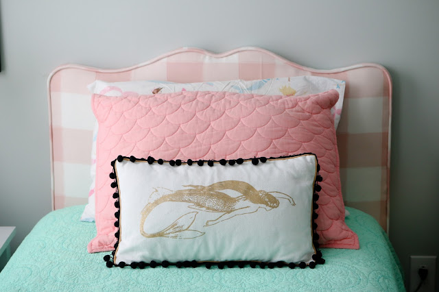DIY upholstered headboard with pink buffalo check fabric and mermaid pillow with pom pom fringe