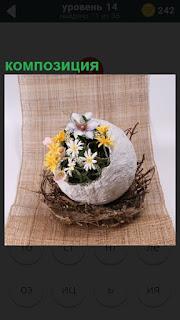 На рогожке поставлена ваза с разными цветами в плетенную корзинку