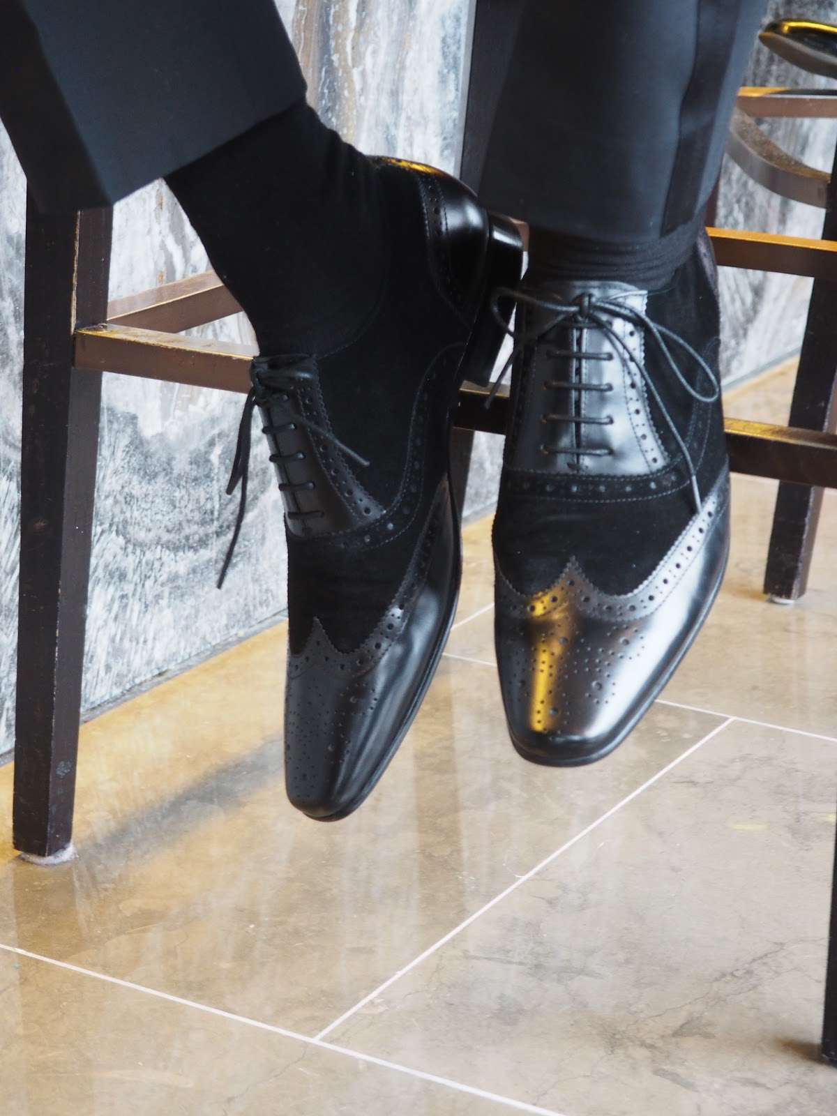 Shoes leaning against a chair with a marble background