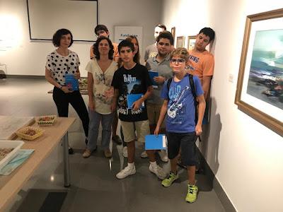 7 participantes de la Asociación junto con Victoria y Beatriz, posan en la Sede de la Fundación Cajasol  junto a uno de los cuadros de Povedano.