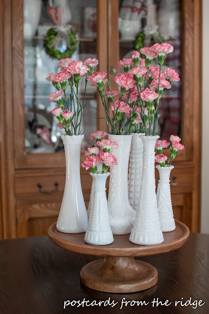 Pretty centerpiece with vintage milk glass vases and carnations on a wooden cake stand. Love!