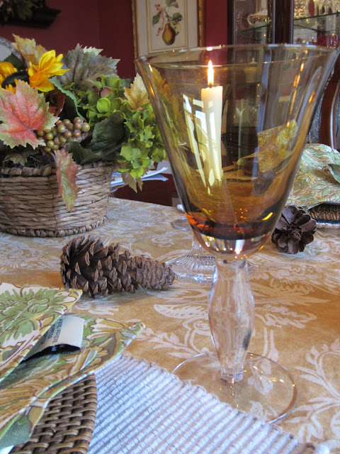 Thanksgiving table with pine cones and amber glasses