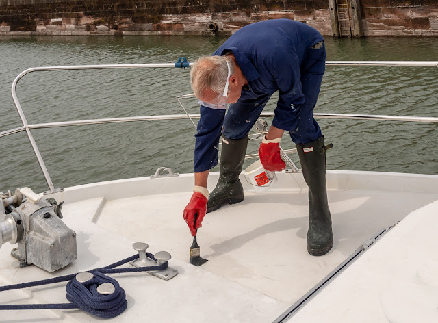 Photo of Phil applying oxalic acid to Ravensdale's foredeck