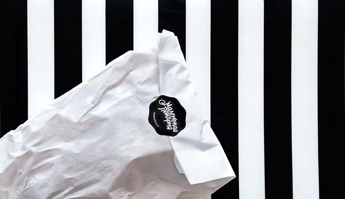 Brot verpackt in weißer Papiertüte mit schwarzem Aufkleber