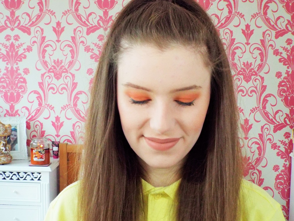 Smiling and looking down to show eye shadow look on the lid