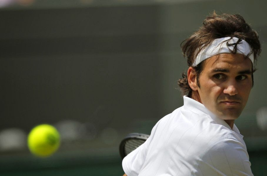 Roger Federer of Switzerland returns to Tommy Robredo of Spain during their men's singles match at the All England Lawn Tennis Championships in Wimbledon, London, Tuesday July 1, 2014.