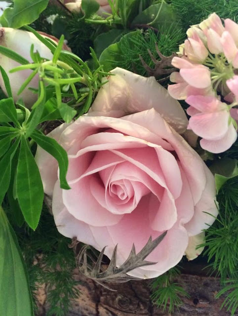 Close up of pale pink rose in wedding floral arrangement