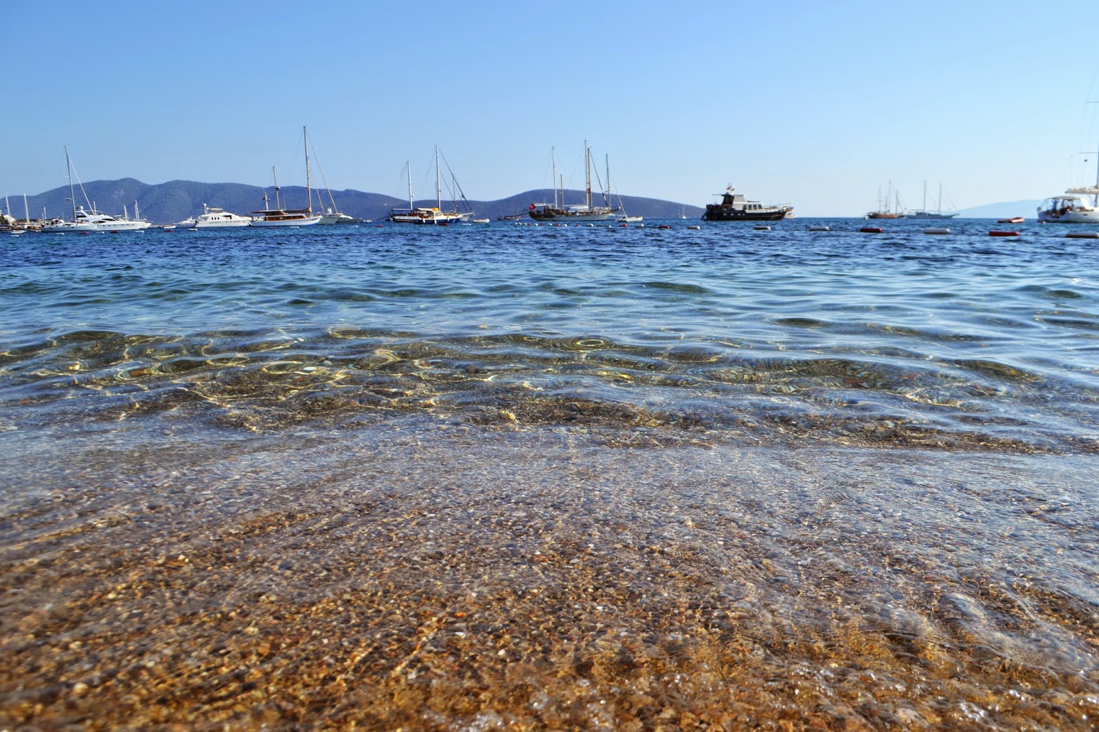 On Bodrum beach looking across to the harbour, boats can be seen in the background