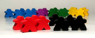 In the foreground is a group of four red meeples next to a group of four black meeples. In the background can be seen a cluster of meeples, with the ones on the left in blue, the ones next to those in purple, then green, and the ones on the right are yellow.