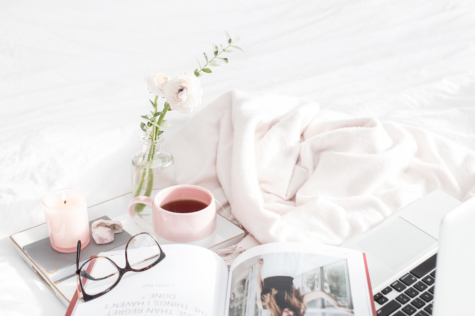 Pink candle and crystals on a bed with white bedding, glasses, cup of tea, magazine and laptop