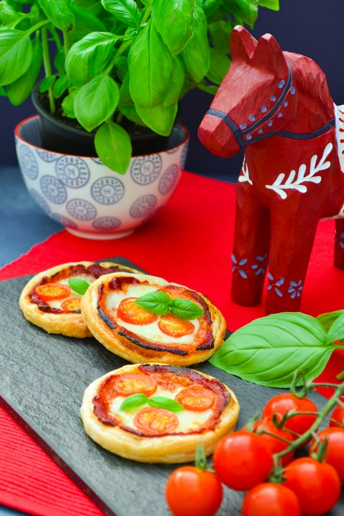 Three Mini Margherita Puff Pizza Pies topped with a sprig of fresh basil