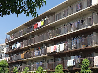 Multiple futons hanging over the balcony to air in a large apartment block