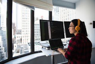 A woman programs on macs in a skyview office in a city