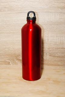 Eine rote Aluminiumflasche mit einem schwarzen Schraubverschluss