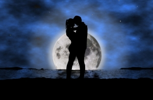 Siluetas de un hombre y una mujer, abrazados en una playa, con una gran luna llena en el horizonte.