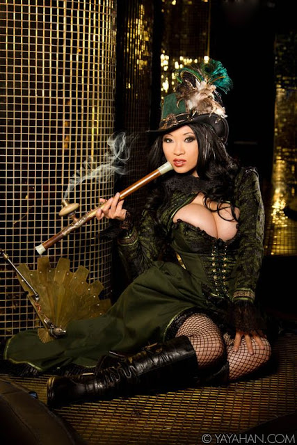 Shanghai Steampunk Madam smoking an opium pipe with metal steampunk fan, green skirt with matching corset, bolero and hat. Fishnet stockings, boots. Women's steampunk clothing