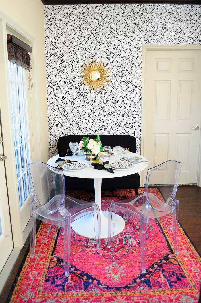 A boring and small beige dining space in an apartment gets a glam makeover! No paint or power tools were needed, but the end result is gorgeous. Tanzania inspired spotted wallpaper, IKEA docksta table, bright pink rug and more. Love that starburst mirror!