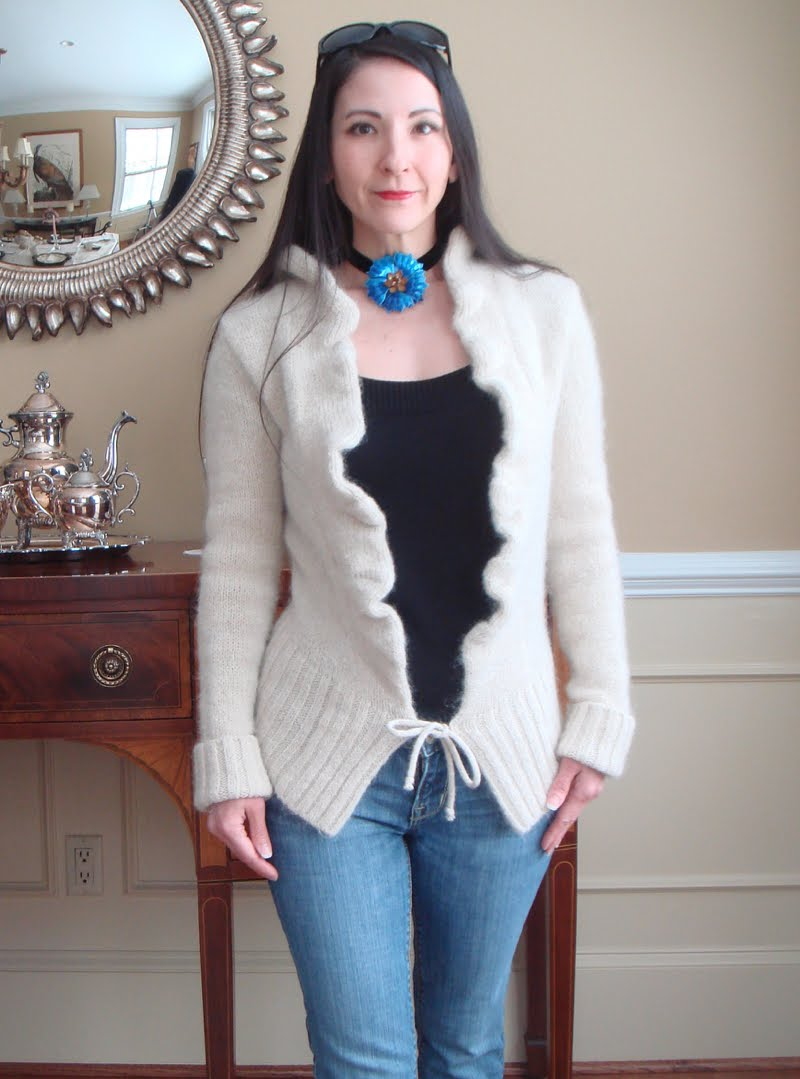 Wearing black velvet choker with a large blue flower in the center. Black top and beige open cardigan with jeans. Black sunglasses on head.