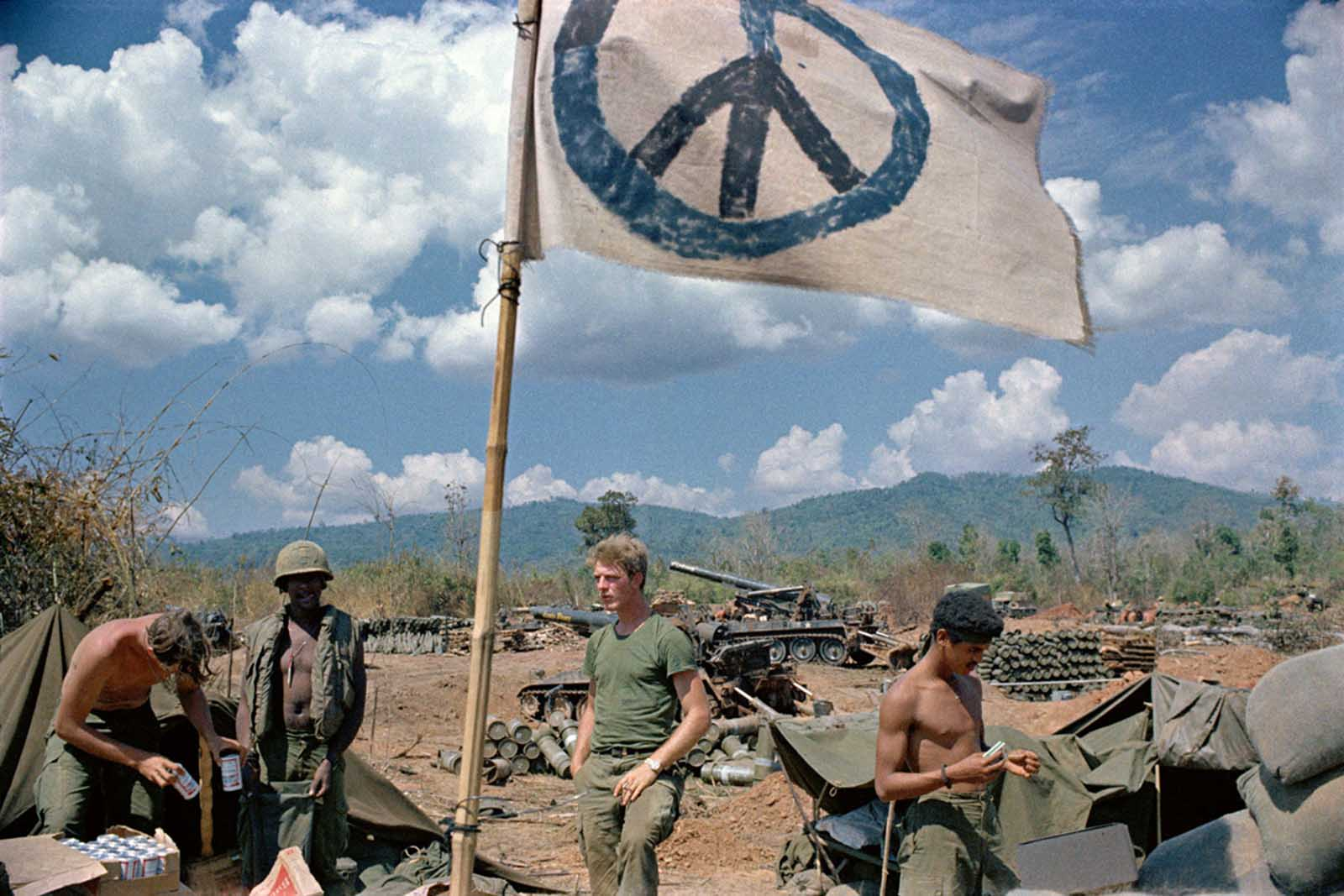 U.S. artillerymen relax under a crudely made peace flag at the Laotian border in 1971. The gunners were giving covering fire for South Vietnamese troops operating inside Laos.