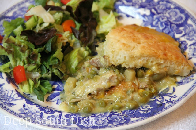 Chicken Pot Pie Casserole with a filling made of pre-cooked chicken, cream soup and chicken broth, canned veggies and a few herbs and seasonings, topped with a biscuit batter.