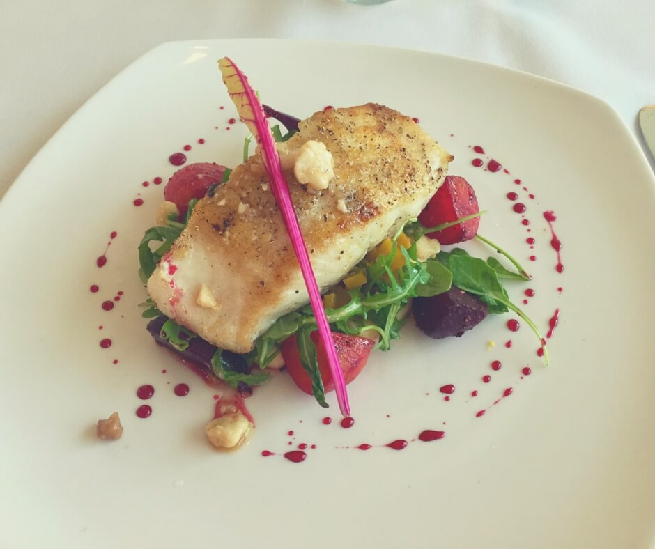 A plate of food, containing Seabass on a bed of salad.