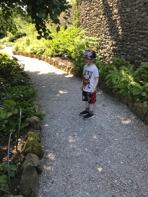 Little boy standing on the gravel path