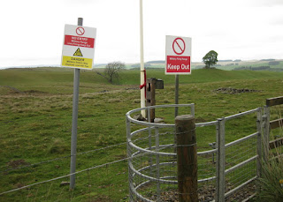Military firing range warning signs posted at a gate, Yorkshire Dales, England