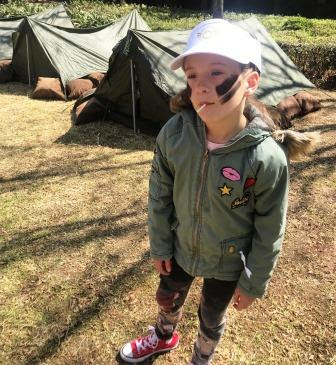 Girl standing in front of army tents