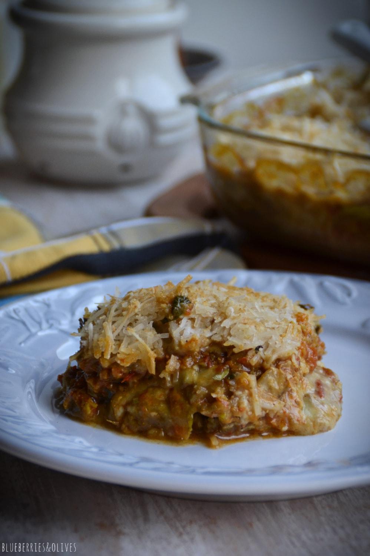 Trozo de lasaña cortado sobre plato blanco, Lasaña de berenjenas en fuente de cristal sobre tabla de madera, con ingredientes de fondo, hierbas aromáticas, laurel seco, molinillo pimienta