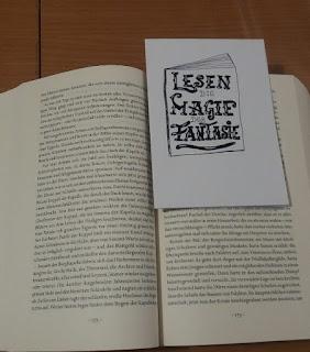 Das Bild zeigt ein aufgeschlagenes Buch mit dem Lesezeichen drin
